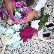 Maha's father showing me what is inside his daughters' bag in Kara Tepe camp, Lesvos, Greece