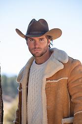 hot young cowboy in a shearling coat outdoors