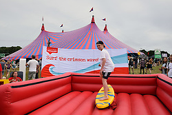 ActionAid fundraising, Latitude Festival 2016, Henham Park, Suffolk, UK. Whoever can stay on the surfboard the longest over the weekend wins a pair of tickets to Latitude 2017