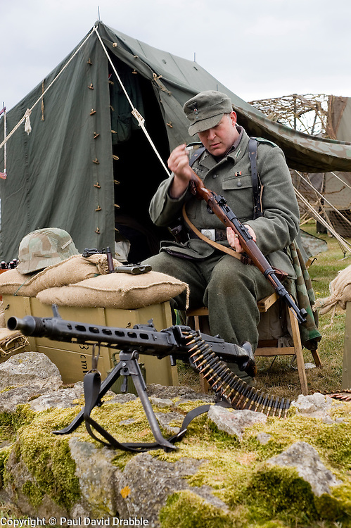 A reenactor from the Northern World War Two Association portraying  life in the field for a German Soldier with the 21st Panzer Division as he sits cleaning a Bolt action Mauser K98 rifle. In the foreground is an MG42 machine gun.<br /> Scarborough Castle<br /> Sunday 30th May 2010<br /> Image © Paul David Drabble