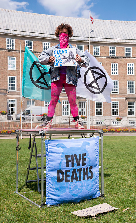 """© Licensed to London News Pictures;23/06/2020; Bristol, UK. Extinction Rebellion's Five a Week campaign for clean air stages a symbolic, theatrical action highlighting the number of premature deaths in Bristol due to air pollution. They have set up 5 cubes on College Green in front of City Hall with the message """"In Bristol, air pollution causes 5 deaths each week"""". People are invited to take part and bring their own placard and message around air pollution and step on top of a cube for 2 minutes in silence, then allow the next person to take their place until the """"death count"""" comes to 296. Participants are then invited to place their placards on the Green to create a sticking sea of messages. Social distancing measures are in place and everyone is required to participate wearing a mask. Extinction Rebellion demand urgent action from Bristol City Council & WECA (West of England Combined Authority) to protect people's lungs and protect the planet, saying health is intrinsically linked to the health of the environment. XR want Clean Air Equality for Life, not just for the coronavirus Covid-19 lockdown, saying we have a unique opportunity as we come out of lockdown to envision a Bristol that puts people's health and the health of the planet first, and put pressure on elected officials to help build the city back better. Photo credit: Simon Chapman/LNP."""