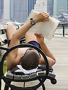 man reading on a bench with in the background downtown New York