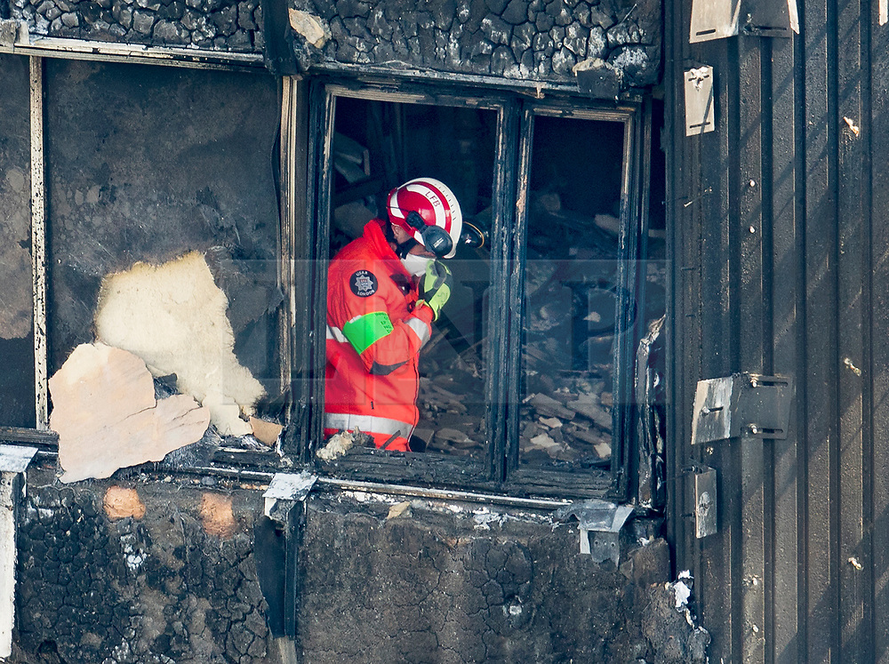 © Licensed to London News Pictures. 18/06/2017. London, UK. A member of London Fire Brigade's Urban Search and Rescue Team feels the heat as he works on the 11th floor of the fire ravaged Grenfell tower block. The blaze engulfed the 27-storey building killing dozens - with 34 people still in hospital, many of whom are in critical condition. The fire brigade say that they don't expect to find anyone else alive. Photo credit: Peter Macdiarmid/LNP