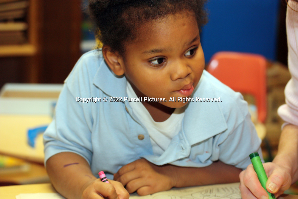 Young African American girl coloring pictures with crayons on a desk