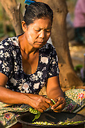 "01 MARCH 2014 - MAE SOT, TAK, THAILAND:  A Burmese woman shells beans in her community in the forest just north of Mae Sot. Mae Sot, on the Thai-Myanmer (Burma) border, has a very large population of Burmese migrants. Some are refugees who left Myanmar to escape civil unrest and political persecution, others are ""economic refugees"" who came to Thailand looking for work and better opportunities.   PHOTO BY JACK KURTZ"