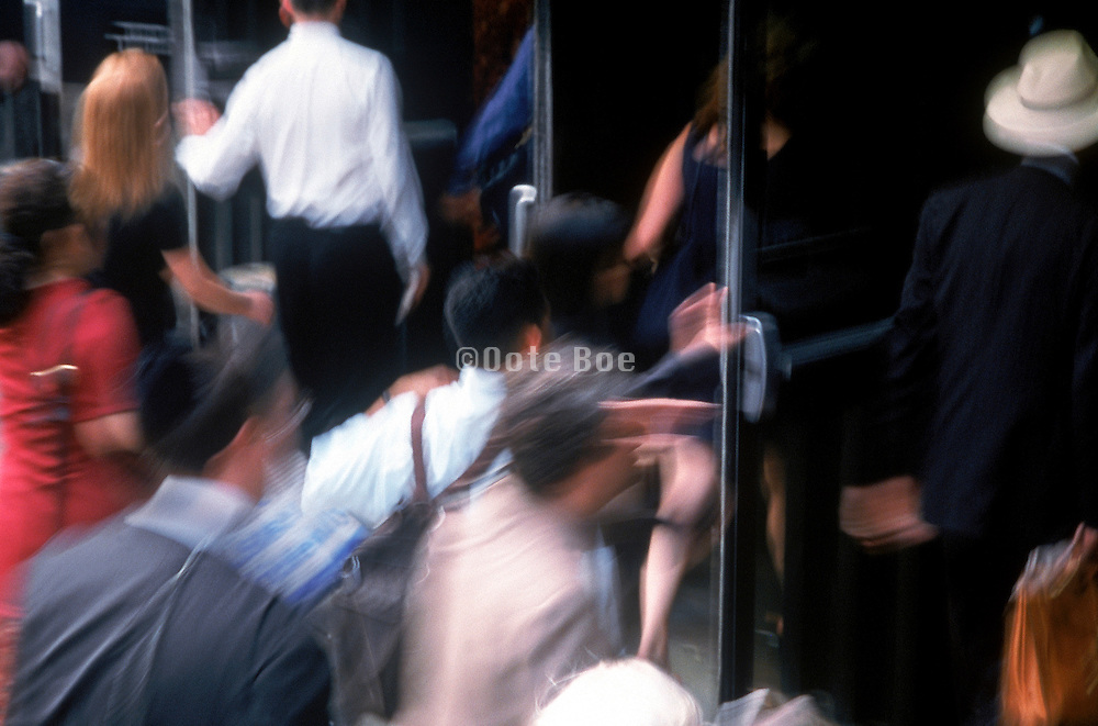 A blurred rush of people entering a building though glass doors
