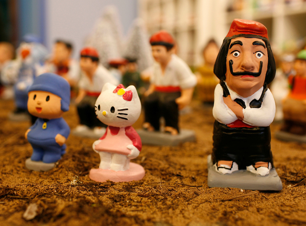 """Torroella de Mongri, Spain, 19 November 2009. .A company in Torroella de Montgrí (Girona, Spain) called """"caganer.com"""" specialized in the production of """"caganers"""" unveiled today  the new figures for Christmas as cartoon Hello Kitty and surrealist painter, Salvador Dali..A """"Caganer"""" is a small figure from Catalonia, usually made of fired clay,  and depicted as squating person in the act defecating. .""""Caganer"""" is Catalan for pooper. It fomrs part of one of the typical figures of  the manger or """"Nativity"""" scene together with Mary, .Joseph and the baby Jesus but hidden in a corner. It is a humorous figure, originally portraying a peasant wearing a .barretina (a red stocking hat), and seems to date from the 18th century when it  was believed that the figure's depositions  .would fertilize the earth to bring a properous year. With  the course of the time, the original  personage of this pooping figure .was  substituted with personalities from the political and sports world and other famous personalities."""