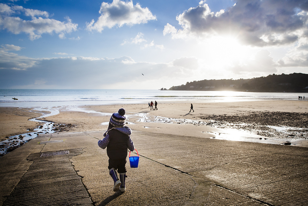 Little boy walking down the slipway with his bucket onto St Brelade's Bay on a wintry day with low sunlight in Jersey, Channel Islands