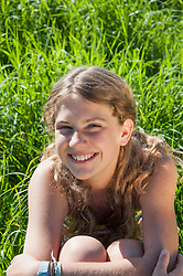 Girl (12-13) sitting in meadow, portrait, close-up