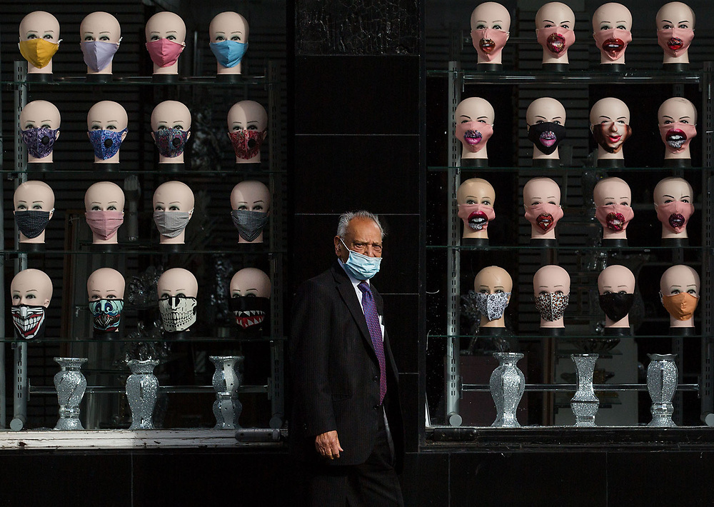 """A man wearing a mask walks past a Glasgow shop selling masks. Today there is an anti-Coronavirus Act protest in George Square, Glasgow.A group of people is expected to gather in George Square to """"protest for their rights back"""". <br /> <br /> Picture Robert Perry 30th August 2020<br /> <br /> Must credit photo to Robert Perry<br /> FEE PAYABLE FOR REPRO USE<br /> FEE PAYABLE FOR ALL INTERNET USE<br /> www.robertperry.co.uk<br /> NB -This image is not to be distributed without the prior consent of the copyright holder.<br /> in using this image you agree to abide by terms and conditions as stated in this caption.<br /> All monies payable to Robert Perry<br /> <br /> (PLEASE DO NOT REMOVE THIS CAPTION)<br /> This image is intended for Editorial use (e.g. news). Any commercial or promotional use requires additional clearance. <br /> Copyright 2018 All rights protected.<br /> first use only<br /> contact details<br /> Robert Perry     <br /> <br /> no internet usage without prior consent.         <br /> Robert Perry reserves the right to pursue unauthorised use of this image . If you violate my intellectual property you may be liable for  damages, loss of income, and profits you derive from the use of this image."""