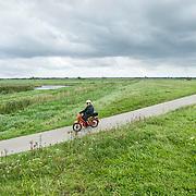 Nederland Delft 17-09-2010 20100917     A4 Delft - Schiedam wordt definitief verlengd,  er  is begin deze maand officieel besloten tot de aanleg van het stuk snelweg waarover zo'n vijftig jaar is gesproken. Natuurgebied dat in de toekomst zal moeten wijken na het doortrekken van de A4, man op brommer bromfiets in het gebied. Rijkswaterstaat en het ministerie van VWS hebben dat laten weten.Over de nieuwe verkeersader wordt al decennialang gesteggeld, vooral omdat de weg het natuurgebied Midden-Delfland doorboort...De zeven kilometer asfalt tussen Delft en Schiedam doorkruist straks verdiept of via een tunnel het natuurgebied tussen de twee steden. Het belangrijkste pluspunt is dat de A13 wordt ontlast. Op rijksweg A13 staat dagelijks de voor de economie schadelijkste file van Nederland. Met het project A4 Delft-Schiedam willen lokale en regionale overheden en het Rijk de problemen rond bereikbaarheid en leefbaarheid op en rond de A13 en de A4 Delft-Schiedam oplossen. Midden Delftland.