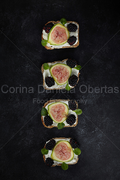 Wholemeal bread with seeds smeared with fresh cheese cream, slices of figs, blackberries and songino leaves.