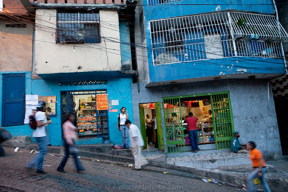 Katherine Navas, a high school student  (behind counter in shop on right), tends to a customer behind the counter of her stepfather's Internet and copy shop in Caracus, Venezuela. (From the book What I Eat: Around the World in 80 Diets.)  Bars on all the windows, doors, and balconies signal that security is a major concern in this neighborhood. Caracas was the murder capital of the world in 2008; 50 murders in one weekend is not unheard of. Local gangs are viciously territorial and ruthless in their victimization of the hardworking, law-abiding majority. Noemi Hurtado, an 83-year-old who has lived a stone's throw from Katherine's house for the past 51 years, has never once crossed into the barrio of La Silsa. ?It's too dangerous,? she says. ?I would never go there.? When Noemi moved to western Caracas, the La Silsa barrio didn't yet exist; the hills surrounding the valley were forested and, she remembers, there were waterfalls