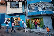 KatherineNavas,ahighschoolstudent(behindcounterinshoponright),tendstoacustomerbehindthecounterofherstepfather'sInternetandcopyshopinCaracus,Venezuela.(FromthebookWhatIEat:AroundtheWorldin80Diets.)Barsonallthewindows,doors,andbalconiessignalthatsecurityisamajorconcerninthisneighborhood.Caracaswasthemurdercapitaloftheworldin2008;50murdersinoneweekendisnotunheardof.Localgangsareviciouslyterritorialandruthlessintheirvictimizationofthehardworking,law-abidingmajority.NoemiHurtado,an83-year-oldwhohaslivedastone'sthrowfromKatherine'shouseforthepast51years,hasneveroncecrossedintothebarrioofLaSilsa.?It'stoodangerous,?shesays.?Iwouldnevergothere.?WhenNoemimovedtowesternCaracas,theLaSilsabarriodidn'tyetexist;thehillssurroundingthevalleywereforestedand,sheremembers,therewerewaterfalls