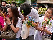 "15 JULY 2011 - PHRA PHUTTHABAT, SARABURI, THAILAND:   People line up to present flowers and candles to the monks during the Tak Bat Dok Mai at Wat Phra Phutthabat in Saraburi province of Thailand, Friday, July 15. Wat Phra Phutthabat is Phra Phutthabat, Saraburi, Thailand, is famous for the way it marks the beginning of Vassa, the three-month annual retreat observed by Theravada monks and nuns. The temple is highly revered in Thailand because it houses a footstep of the Buddha. On the first day of Vassa (or Buddhist Lent) people come to the temple to ""make merit"" and present the monks there with dancing lady ginger flowers, which only bloom in the weeks leading up Vassa. They also present monks with candles and wash their feet. During Vassa, monks and nuns remain inside monasteries and temple grounds, devoting their time to intensive meditation and study. Laypeople support the monastic sangha by bringing food, candles and other offerings to temples. Laypeople also often observe Vassa by giving up something, such as smoking or eating meat. For this reason, westerners sometimes call Vassa the ""Buddhist Lent."" The tradition of Vassa began during the life of the Buddha. Most of the time, the first Buddhist monks who followed the Buddha did not stay in one place, but walked from village to village to teach. They begged for their food and often slept outdoors, sheltered only by trees. But during India's summer rainy season living as homeless ascetics became difficult. So, groups of monks would find a place to stay together until the rain stopped, forming a temporary community. Wealthy laypeople sometimes sheltered monks on their estates. Eventually a few of these patrons built permanent houses for monks, which amounted to an early form of monastery.     PHOTO BY JACK KURTZ"