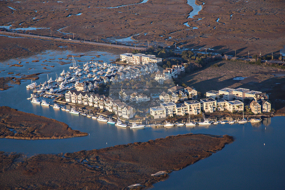 Aerial showing a housing development surrounded by marsh and water in Charleston, SC.