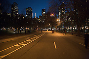 road with people walking through central park at dusk
