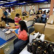 Nederland Rotterdam 11 december 2007 .Werknemers stellen kerstpaketten samen en pakken deze in. Roteb Impact is een sociale werkplaats voor minder validen en geestelijk gehandicapten. ..Roteb heeft banen voor mensen die door psychische, lichamelijke of verstandelijke beperkingen alleen kunnen werken onder aangepaste omstandigheden. Rotterdammers met een handicap en op zoek naar een baan bij Roteb Ultimade, Roteb MultiGroen, Roteb Impact of andere Roteb-onderdelen dienen zich te melden bij het dichtstbijzijnde CWI...Roteb richt zich onder meer op werkgelegenheid, arbeidsintegratie en uitvoering van de Wet sociale werkvoorziening (Wsw). Roteb biedt werk aan mensen die met psychische, lichamelijke of verstandelijke beperkingen alleen kunnen werken onder aangepast omstandigheden. Daarnaast biedt Roteb leerwerkplaatsen voor andere doelgroepen met een afstand tot de arbeidsmarkt om ze meer kans te bieden op een reguliere baan..Roteb biedt in de 4 werkbedrijven, Impact, Montaz, Ultimade en MultiGroen aangepast werk. Daarnaast werken medewerkers individueel gedetacheerd of in een werkunit op locatie bij de klant. Als het nodig is begeleidt Roteb medewerkers die willen en kunnen uitstromen naar de reguliere arbeidsmarkt..Voor zover mogelijk sluit Roteb de mogelijkheden van arbeidsgehandicapten en de vragen op de reguliere arbeidsmarkt op elkaar aan. Daardoor vinden mensen met een lichamelijke, verstandelijke of psychische beperking werk dat bij hen past. We onderhouden intensieve contacten met verwijzende instellingen, belangenorganisaties en praktijkscholen. Onze werkbedrijven hebben veel zakelijke relaties in de markten en springen in op nieuwe mogelijkheden. Zij vernieuwen hun diensten en producten in samenspraak met hun partners.....Roteb divisie multibedrijven is de nieuwe naam voor de werkzaamheden van Multibedrijven en Inderdaad..Multibedrijven is een divisie van de dienst Roteb gericht op werkgelegenheid, arbeidsintegratie en uitvoering van de Wet sociale werkvoorzie