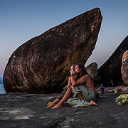 A young couple take a selfie as the sun goes down on Agonda beach. The rock formations at the south end of Agonda beach are a favorite place for people to watch the sunset.