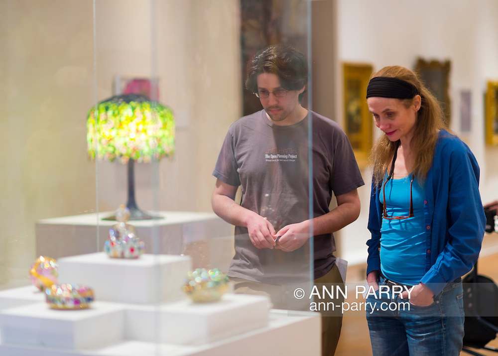 Roslyn, New York, U.S. - April 12, 2014 - During International Slow Art Day, visitors view a rhinestone Minaudiere collection at the Garden Party exhibit at the Nassau County Museum of Art on Long Island. During this annual worldwide event, those participating (not known if those shown are participants) went to local museums and viewed a small number of works of art, each for at least 10 minutes, and then discussed them afterward.