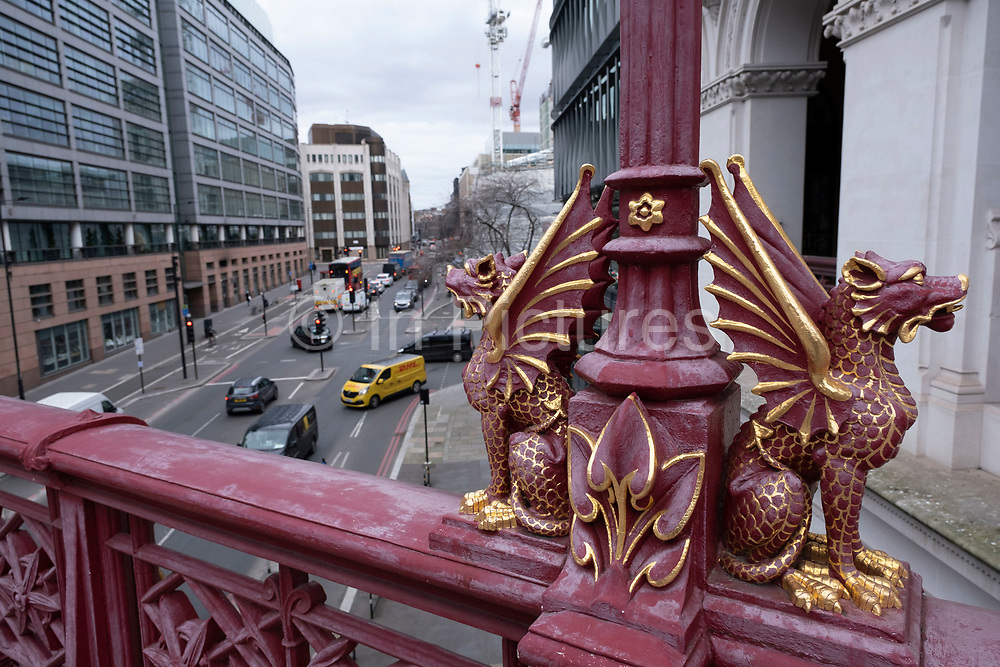 Red and gold dragons sit on the opposite side of the City of London dragon boundary mark at Holborn Viaduct on 5th March 2021 in London, United Kingdom. The dragon boundary marks are cast iron statues of dragons on metal or stone plinths that mark the boundaries of the City of London painted silver, with details of the dragon wings and tongue picked out in red.