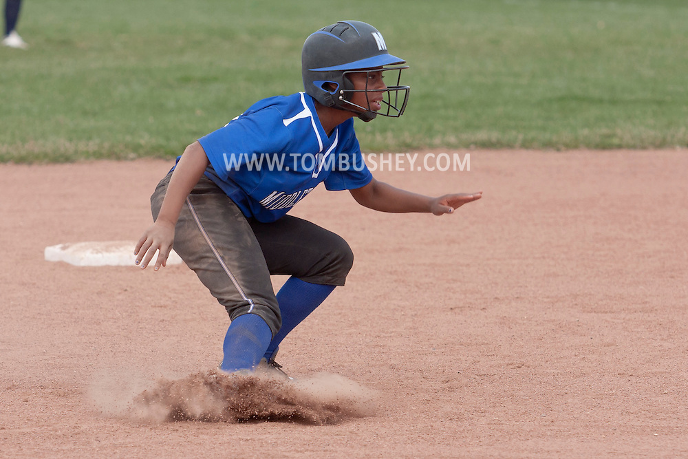 Middletown, New York - A baserunner stops between second and third base during a varsity girls' softball game on April 25, 2014.