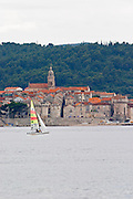 View across the sea on the town of Korcula on the island of the same name where Marco Polo was born. A small sail boat on the water. Korcula Island. Dalmatian Coast, Croatia, Europe.