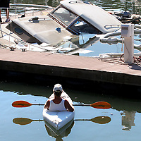 Kayaker Thomas Winters paddled to the X dock at the Santa Cruz Harbor to check out the 1950's era Chris Craft powerboat that sunk in its slip .<br /> Photo by Shmuel Thaler <br /> shmuel_thaler@yahoo.com www.shmuelthaler.com