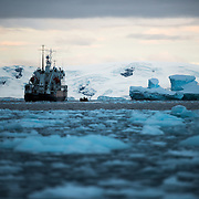 An Antarctic cruise ship in the distance past the brash ice and small icebergs, as evening sets.