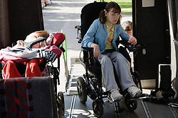 Young girl with physical disability coming off ramp into an ambulance,