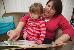 Toddler with her mum  on a sofa reading a book