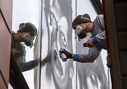 © Licensed to London News Pictures.  18/09/2017; Bristol, UK. VOYDER (and his reflection) paints an image of David Bowie onto the front window of the Colston Hall. Colston Hall, Bristol's largest music venue, is to unveil a new mural painted in partnership with Upfest by Bristol artist Voyder of eight musical legends, each of which have performed at Colston Hall over the last 150 years, to celebrate the Colston Hall's 150th anniversary this week on 20 September.   The giant mural on the glass panes above the main entrance will feature portraits of Ella Fitzgerald, Louis Armstrong, David Bowie, Debbie Harry (Blondie), Jimi Hendrix, Mick Jagger, Sergei Rachmaninoff and Paul McCartney. The mural will be in place in time for Colston Hall to mark its anniversary with a big free Birthday Bash on Wednesday 20 September, exactly 150 years from when the venue first opened, to which all of Bristol is invited. Highlights for the night will include the world-famous Ukulele Orchestra of Great Britain, immersive projections from Limbic Cinema and toe tapping swing music from the Bruce/Ilett Big Band. The free event will begin at 6.30pm and see a complete takeover of the building, giving people the chance to explore every corner, stumbling across musicians, DJs, installations and projections, as acts pop up to create a unique party atmosphere. Colston Hall first opened its doors to the public on the 20th September 1867, after The Colston Hall Company bought the land from Colston Boy's School in 1861 to fulfil their vision of building a concert hall in the city. The Hall has seen four iterations in its 60 years, with the fourth and present Colston Hall opening in 1951. Picture credit : Simon Chapman/LNP