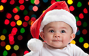 A cute 5 month old baby boy with a santa hat and Christmas lights.