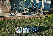 Freshly cleaned athletic shoes, bicycles and two feral cats near migrant worker housing on the property of a large greenhouse operation just outside of Leamington. The building houses Jamaican temporary workers.