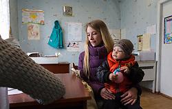 Olga Malishenko, 23, and her son Vladislav, 2yrs 7 months, consult with Dr Marina Shcherbakova at the Bolshaya Vergunka polyclinic, Lugansk, where MSF are holding a mobile clinic for local residents.