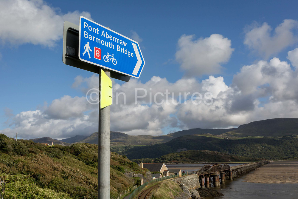 Signpost pointing down towards Barmouths pedestrian and rail bridge on the Mawddach Estuary, on 13th September 2018, in Barmouth, Gwynedd, Wales.
