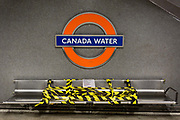 As the UKs Conornavirus pandemic lockdown continues, but with travel restrictions and social distancing rules starting to ease after three months of closures and isolation, hazard tape blocks some seating beneath the station name, at London Undergrounds Canary Water station, on 9th June 2020, in London, England.