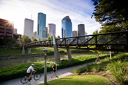 A jogger and cyclists enjoying a sunny day on the Hike & Bike Trail along Buffalo Bayou Park with the Houston, Texas skyline in the background.