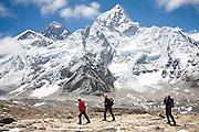 Trekkers walk alongside a dramatic backdrop of Mount Everest (8848m) and Nuptse (7861m) on Kala Patthar (5545m), for many the final destination on the Everest Base Camp Trek, Khumbu region, Sagarmatha National Park, Himalaya Mountains, Nepal.