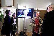 Tijdens de avond van de verkiezingsuitslag in het gemeentehuis van Utrecht kijken twee vrouwen naar de televisie, terwijl kandidaat PVDA-raadslid Bram de Goede (rechts met biertje) een gesprek heeft.