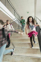 School students running down stairs, Bavaria, Germany
