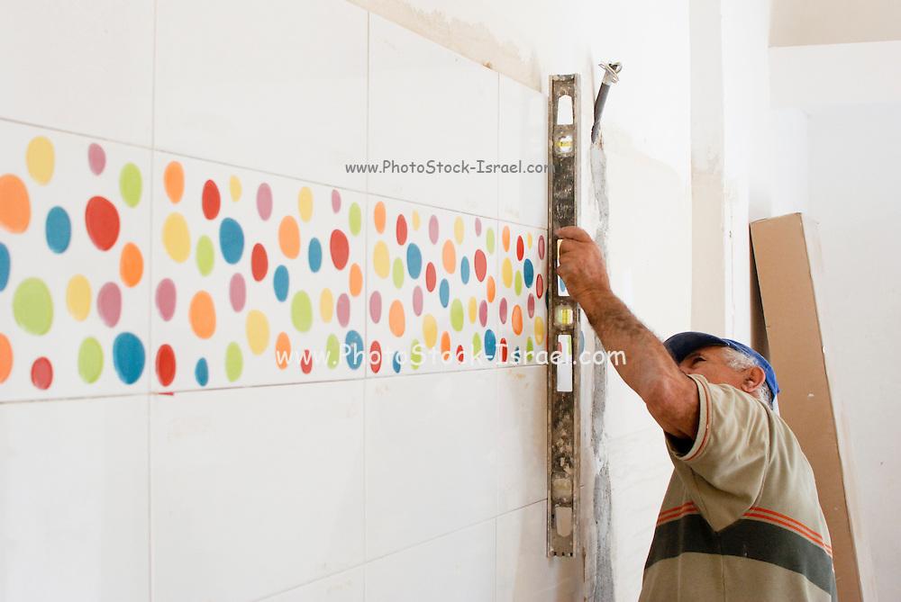skilled Tiler at work laying tiles