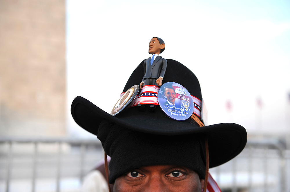Sporting a hat peppered with Obama pins and a doll, Dr. Donald Torver, who traveled from San Francisco for the ocassion, looks out from his elevated perch by the Washington Monument at 6am on the day of Barack Obama's historic Presidential inauguration on January 20, 2009.  An estimated two million people flocked to Washington D.C. for the ceremony, enduring freezing temperatures to witness Obama take the oath of office becoming the first African-American to become President, the 44th in the history of the U.S.