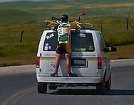 A cyclist hitches a ride on the sag wagon back to the start at the Copperoplis Road Race in the tiny community of Wilton in Calaveras County, CA.