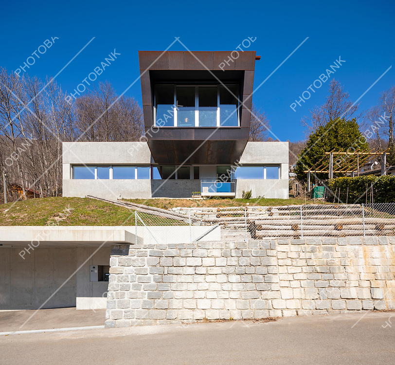 Frontal view of modern isolated villa, surrounded by nature. Iron and concrete cladding. Nobody inside