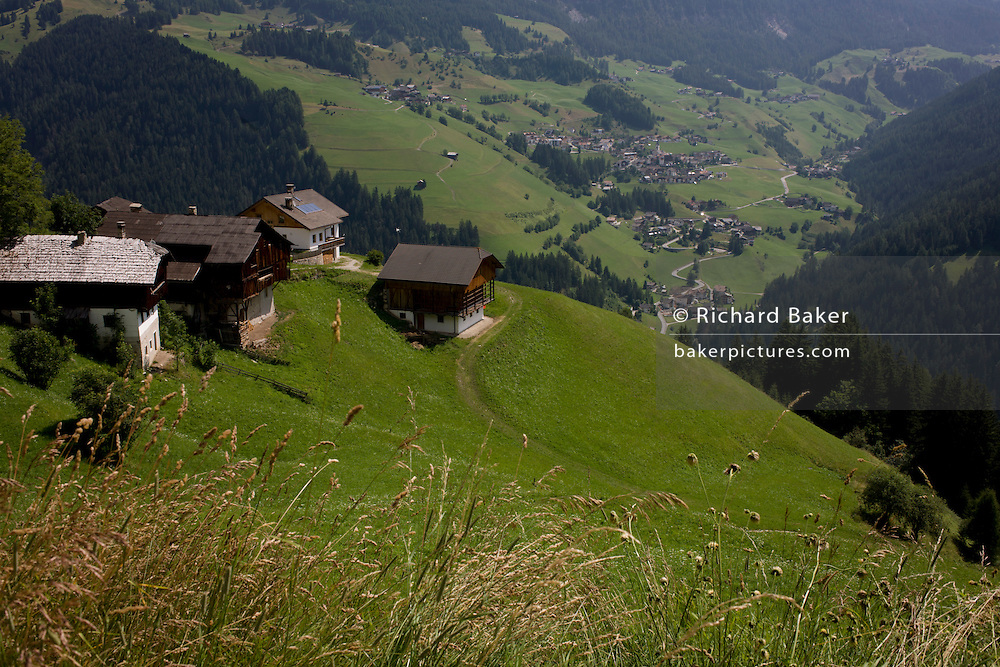 Mountainside barns overlooking the valley below at Picedac near Wengen-La Val, in Alta Badia, south Tyrol, Italy.