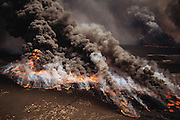 Aerial of burning Al Burgan oil fields in Kuwait after the end of the Gulf War in May of 1991. More than 700 wells were set ablaze by retreating Iraqi troops creating the largest man-made environmental disaster in history.