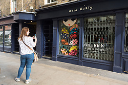 © Licensed to London News Pictures. 19/09/2018. London, UK.  A woman wearing an Orla Kiely bag take a photo outside of a closed Covent Garden store as Orla Kiely £8 million retail empire collapses. It was reported the company ceased trading earlier this week with immediate job losses and unpaid staff wages. Photo credit: Ray Tang/LNP