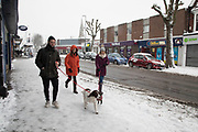 People out on Kings Heath High Street during heavy snow fall on Sunday 10th December 2017 in Birmingham, United Kingdom. Deep snow arrived in much of the UK, closing roads and making driving treacherous, while many people simply enjoyed the weather.