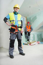Two construction workers at construction site of new building